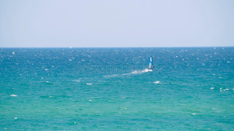 Windsurfer riding the waves in the sea. Shot. Windsurfer in the sea, man on windsurf conquering the waves, enjoying. Extreme sport, active lifestyle, happy stock image