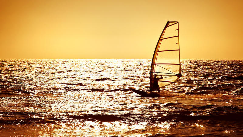 Windsurfer silhouette over sea sunset royalty free stock image