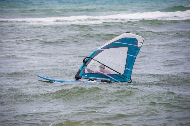 windsurfer z deską na tropikalnej plaży, robi wodnemu początkowi obraz royalty free