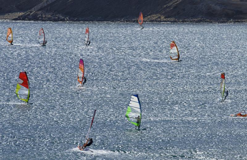 Windsurfers rides on the brilliant waves of the beautiful Mediterranean sea. On Cape Prasonisi Rhodes, Greece royalty free stock photography