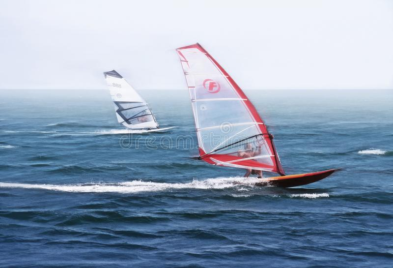 Windsurfers riding the waves of the beautiful blue sea. The photo shows windsurfers riding on the waves of the beautiful blue sea in clear Sunny weather stock image