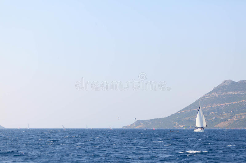 Windsurfers and Sailing yacht. Several windsurfers sail across the channel near Korcula stock images