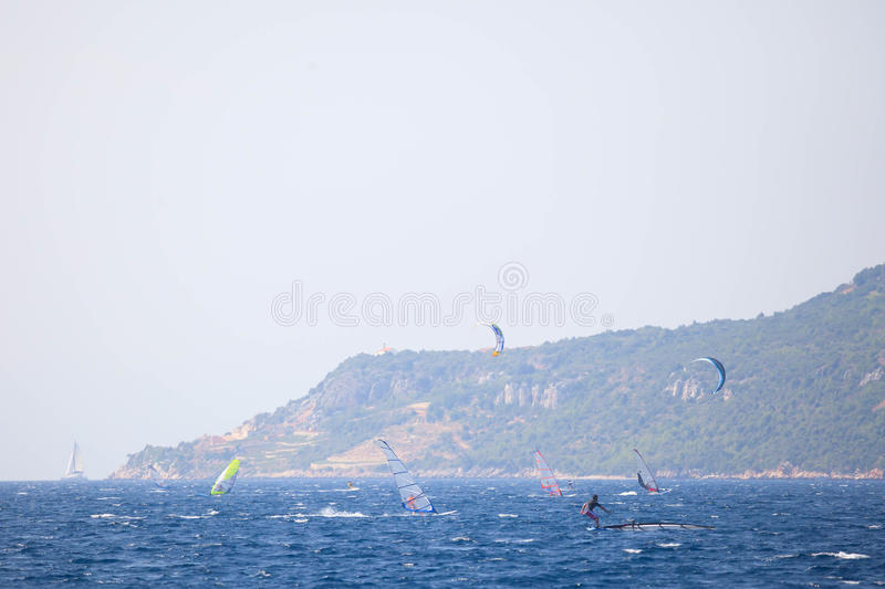 Windsurfers and Sailing yacht. Several windsurfers sail across the channel near Korcula royalty free stock images