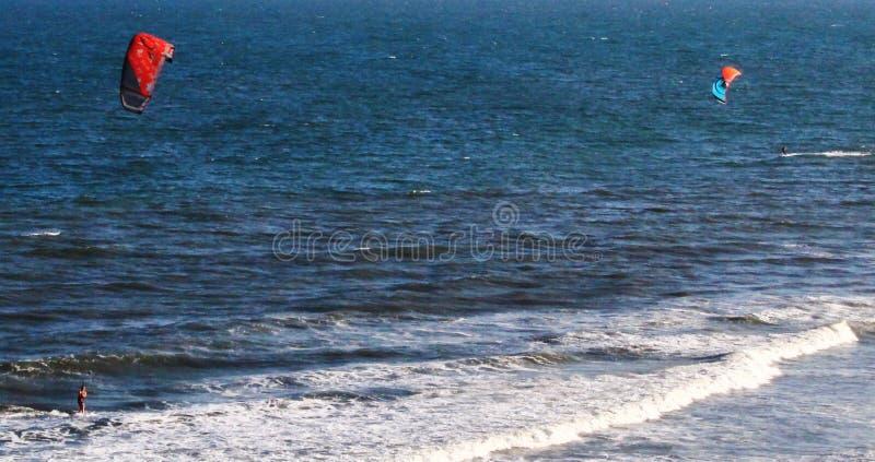 2 windsurfers-SC. 2 windsurfers on the Atlantic Ocean at Folly Beach in SC stock image