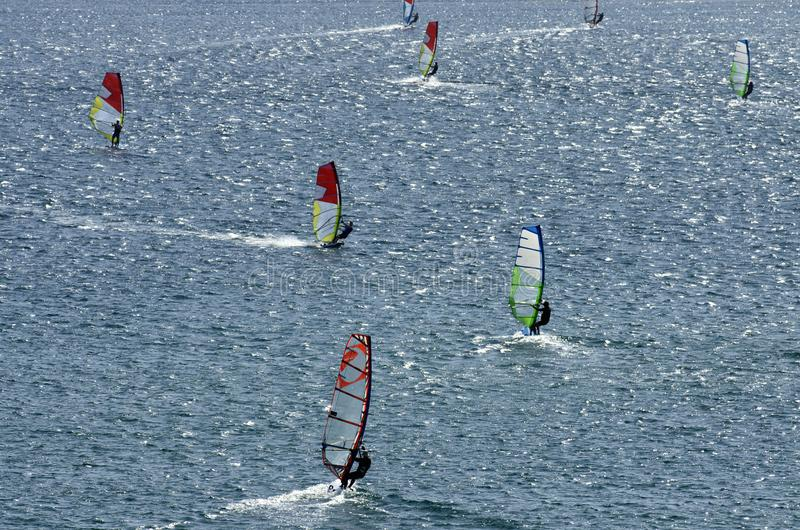 Windsurfers on the sparkling waves of the Mediterranean sea. Windsurfers on the shining waves of the Mediterranean sea at Cape Prasonisi Greece royalty free stock photo