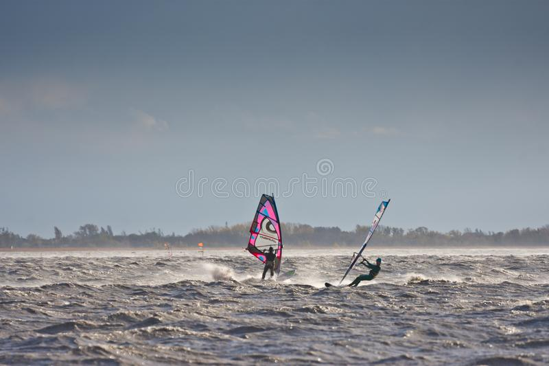 Windsurfers in a storm. BURGENLAND, AUSTRIA - OCTOBER 29, 2017: Windsurfers meet each other on the Neusiedlersee Lake Neusiedl struggling with strong wind, spray stock photos