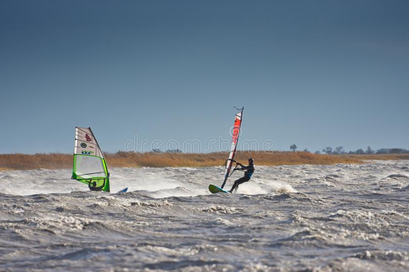 Windsurfers in a storm. BURGENLAND, AUSTRIA - OCTOBER 29, 2017: Windsurfers meet each other on the Neusiedlersee Lake Neusiedl, struggling with strong wind stock images