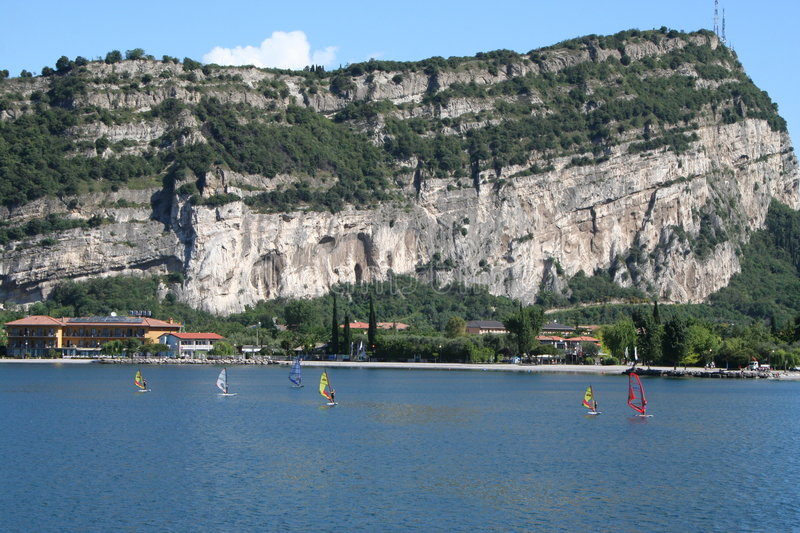 Windsurfers,Torbele, Lake Garda, Italy. Windsurfers practice on a placid lake Garda, dominated by a spectacular limestone outcrop royalty free stock photo