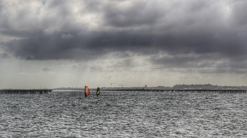 Windsurfers. Under the clouds stock photo