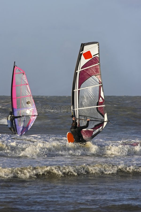 Windsurfing. Water sport as two windsurfers surf the waves stock photos