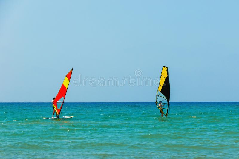 Windsurfing on the background of the sea landscape and clear sky.Two windsurfers men go in for sports, copy space.  stock photo