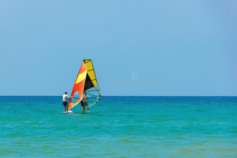 Windsurfing on the background of the sea landscape and clear sky.Two windsurfers men go in for sports, copy space.  royalty free stock photos
