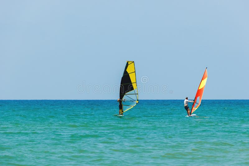 Windsurfing on the background of the sea landscape and clear sky.Two windsurfers men go in for sports, copy space.  royalty free stock photography