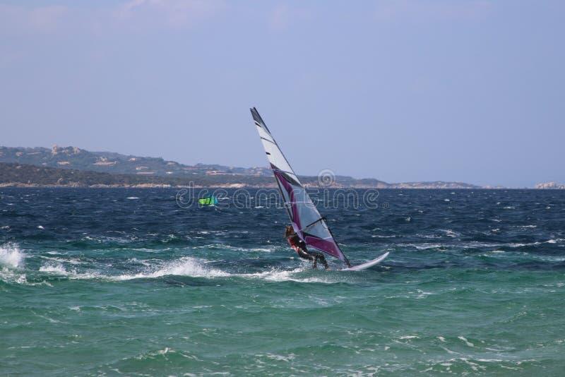 Windsurfing dziewczyna sunie nad błękitnym choppy morzem Porto Pollo, Sardinia, Włochy fotografia stock