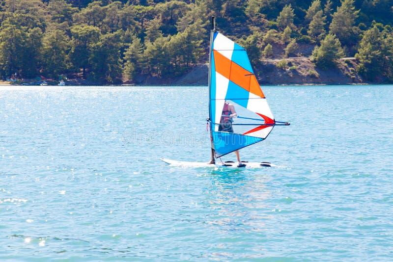 windsurfing Een watersportman op een sailboard stock afbeelding