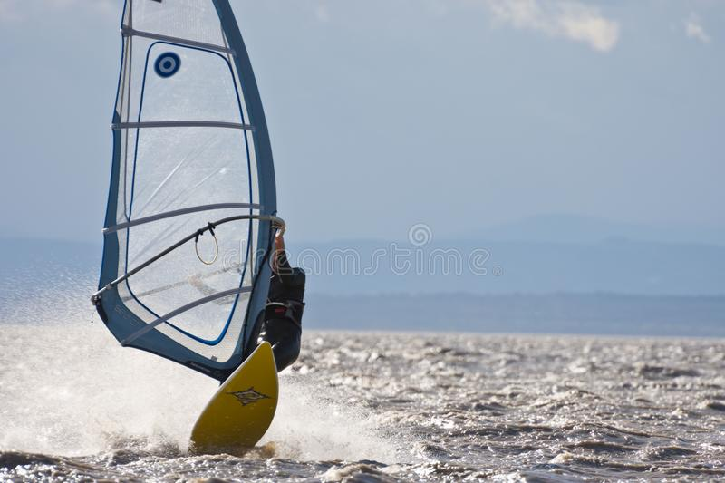 Windsurfing high speed. BURGENLAND, AUSTRIA - OCTOBER 29, 2017: Windsurfer on the Neusiedlersee Lake Neusiedl performing high speed surfing in strong wind, spray stock photography