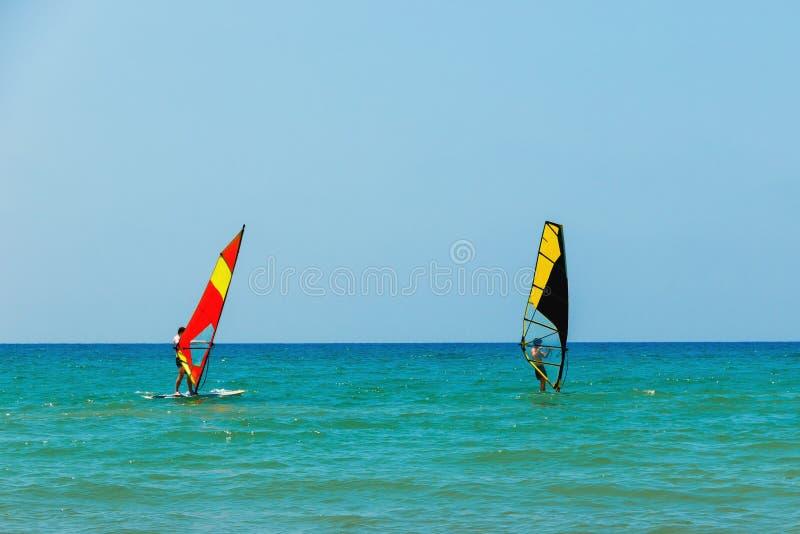 Windsurfing na tle denny krajobraz jasny niebo i Dwa windsurfers mężczyzny iść wewnątrz dla sportów, kopii przestrzeń zdjęcie stock