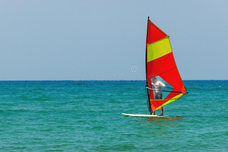 Windsurfing op de achtergrond van het overzeese landschap en de duidelijke hemel Het Windsurfermannetje gaat binnen voor sporten, stock foto