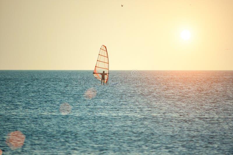 Windsurfing op de overzeese oppervlakte bij zonsondergang in de zon, het concept openluchtactiviteiten stock fotografie