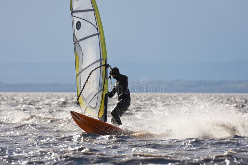 Windsurfing power jibe. BURGENLAND, AUSTRIA - OCTOBER 29, 2017: Windsurfer on the Neusiedlersee Lake Neusiedl performing a power jibe in strong wind, spray and stock photos
