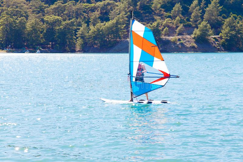 Windsurfing. A water sportsman on a sailboard stock image