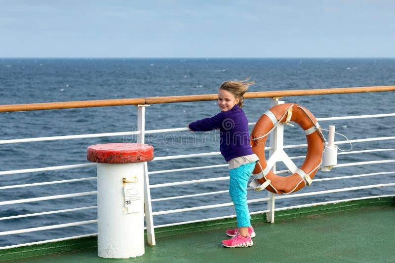 Windswept liten flicka som hänger till räcket av färjan royaltyfri foto