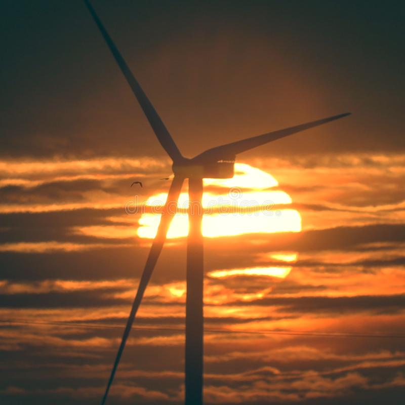 A windturbine across de sun and clouds royalty free stock photos