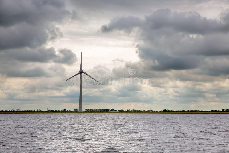 Windturbine bij Nederlandse kust met het bedreigen van donkere hemel royalty-vrije stock foto's