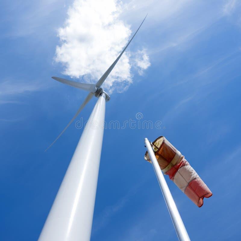 Windturbine en zemel en witte cloudagainst blauwe hemel stock afbeeldingen