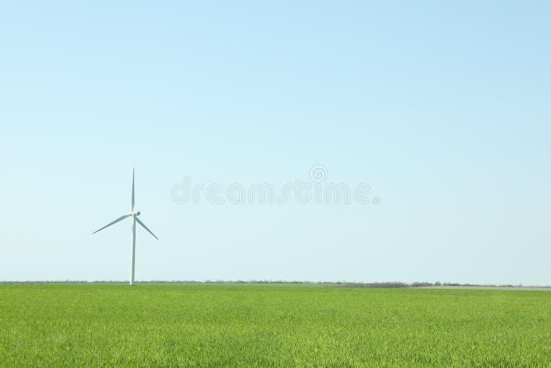 Windturbine op een groen grasgebied, ruimte voor tekst stock afbeelding