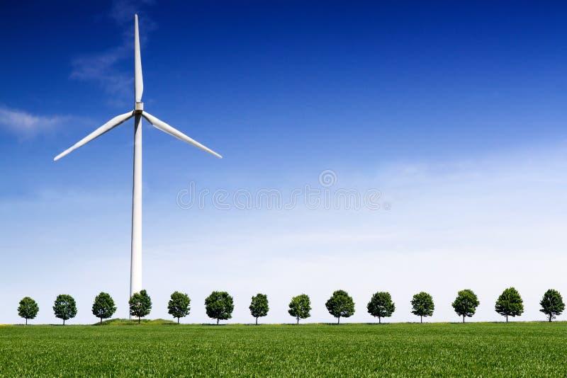 Windturbine op voorzijde van een groen tarwegebied royalty-vrije stock afbeelding