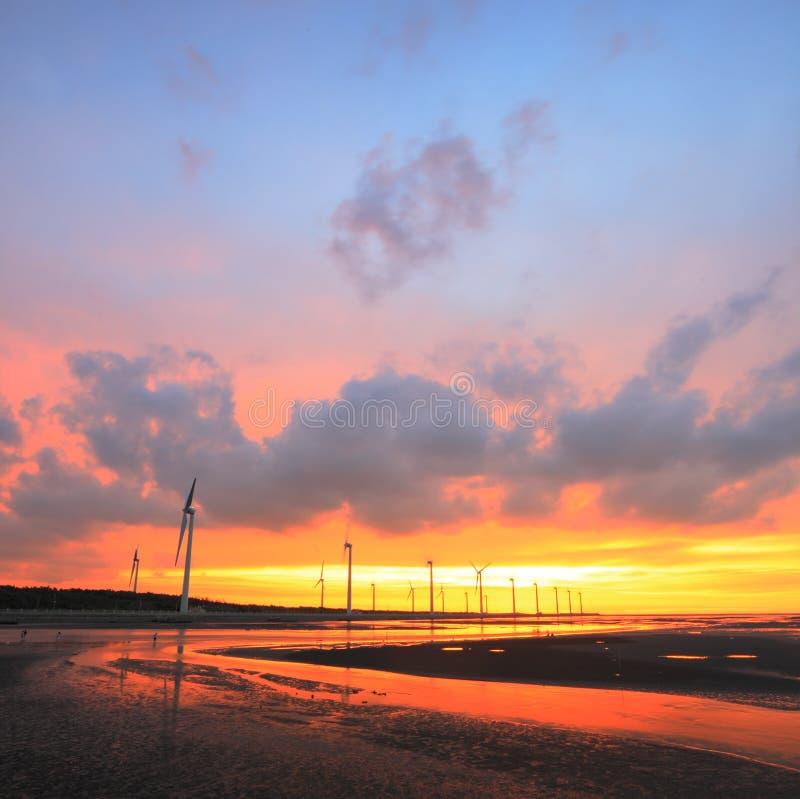 Windturbinen an der Küste unter Sonnenuntergang stockfotografie