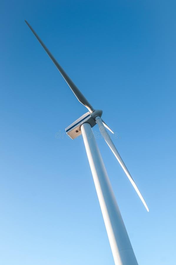 Windturbines die elektriciteit met blauwe hemel produceren stock afbeeldingen