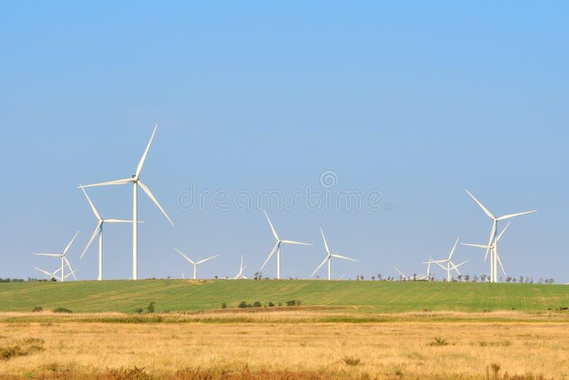 Windturbines die elektriciteit op blauwe hemelachtergrond produceren - Th royalty-vrije stock fotografie