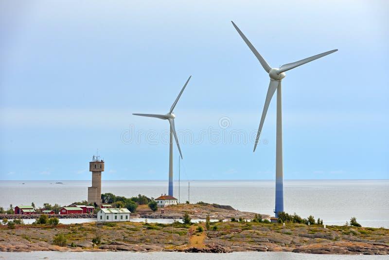 Windturbines en dorp op rotsachtige kusten van Aland-Eilanden op zonsondergang royalty-vrije stock fotografie