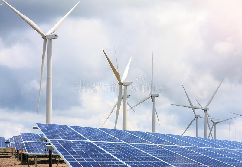 Windturbines en zonnepanelen met de wolken en de hemel stock foto