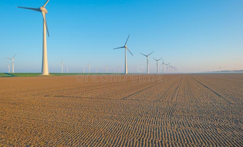 Windturbines langs een dijk bij zonsopgang stock afbeelding