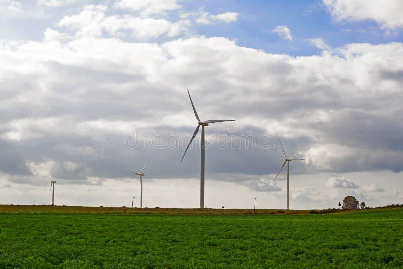 Windturbines met groen gebied en bewolkte hemel stock foto