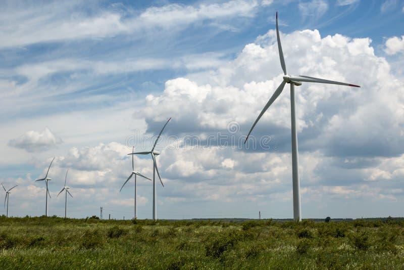 Windturbines tegen mooie bewolkte hemel Duurzame energieproductie stock afbeeldingen