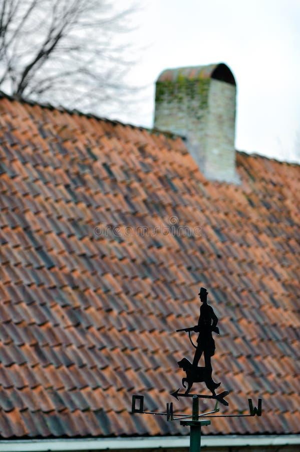 Windvane με τον κυνηγό και το σκυλί απέναντι από την παραδοσιακή στέγη κεραμιδιών κάπου στις Κάτω Χώρες στοκ εικόνα με δικαίωμα ελεύθερης χρήσης