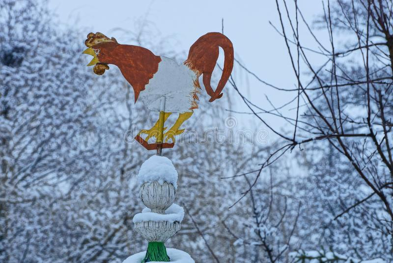 Windwijzer in de vorm van een gekleurde ijzerhaan bij de bovenkant van het dak royalty-vrije stock foto's