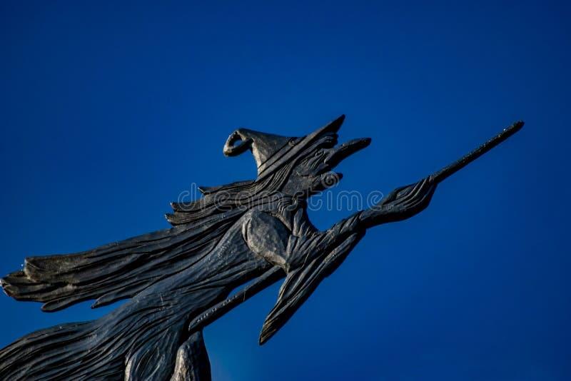 Windwijzer van een heks die op een bezem vliegen stock afbeeldingen