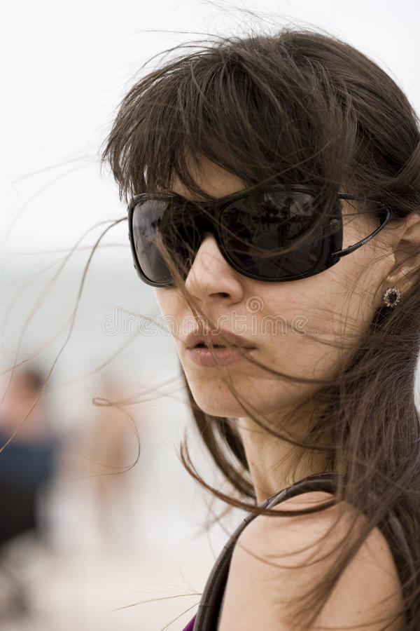 Windy. Face of a young woman in sun glasses during the windy weather on the beach royalty free stock photos
