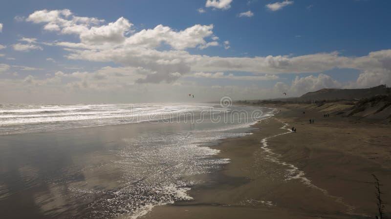 Windy Day na areia larga de Brown encalha na maré baixa Céu nebuloso com o Sun que brilha Silhuetas pequenas de alguns caminhante fotos de stock