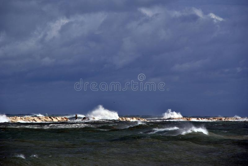 Windy day at sea with big waves against rocks royalty free stock photography