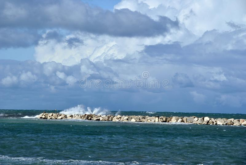 Windy day at sea with big waves against rocks royalty free stock photo
