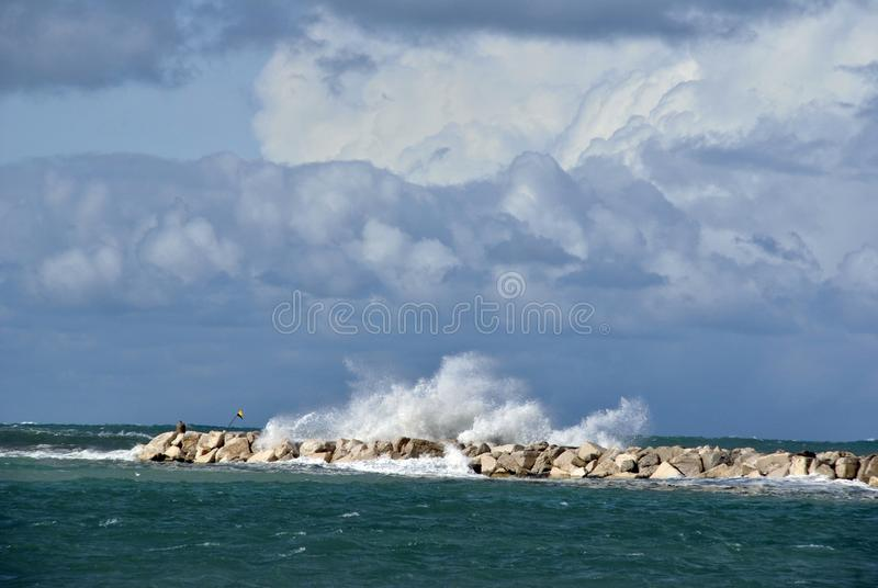 Windy day at sea with big waves against rocks royalty free stock images
