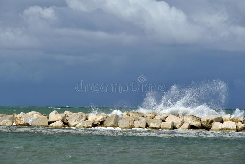 Windy day at sea with big waves against rocks stock photos