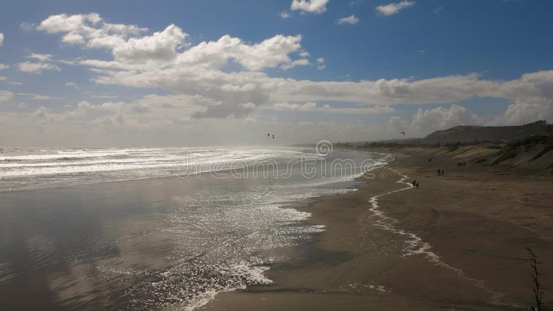 Windy Day sur le sable large de Brown échouent à marée basse Ciel nuageux avec briller de Sun Petites silhouettes de quelques mar photos stock