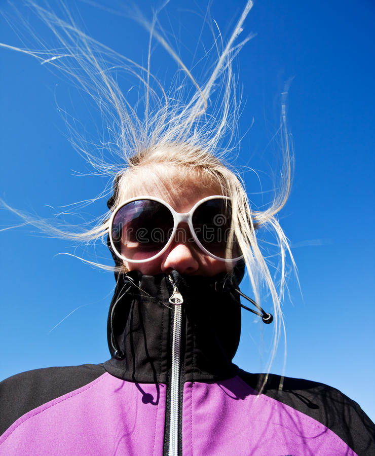 Windy hair. On a girl with sunglasses royalty free stock image